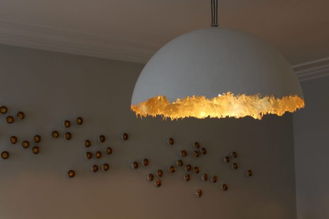 IMAGE: The gold wall art with light in the foreground