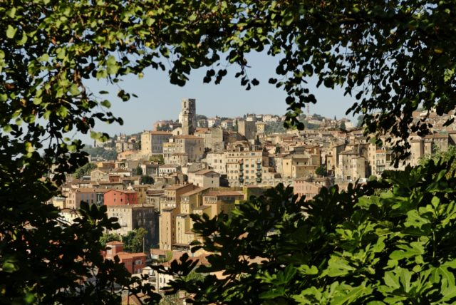 IMAGE: View showing the old town area of Grasse framed by leafy trees
