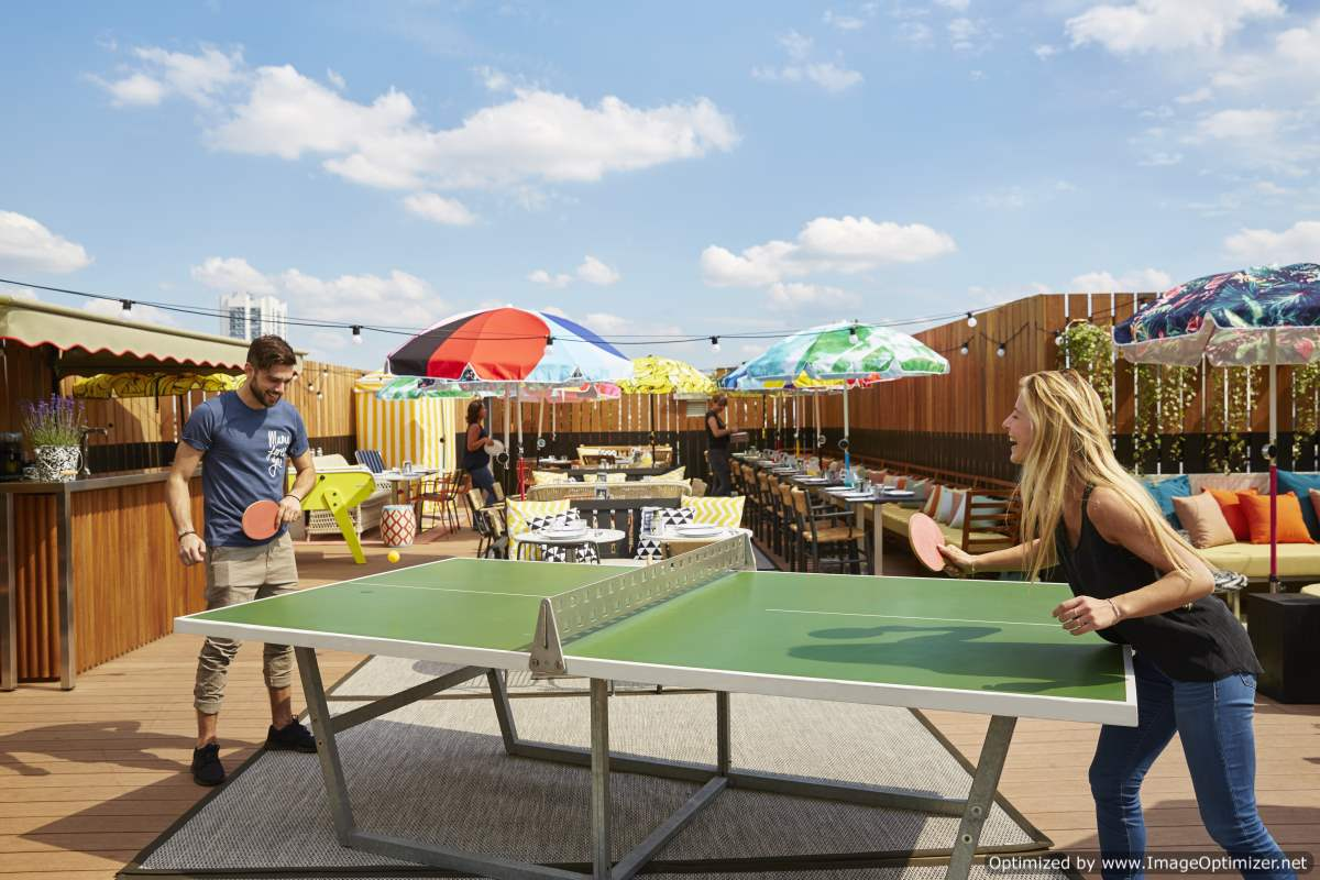 IMAGE: People playing table tennis at Mama Shelter rooftop bar