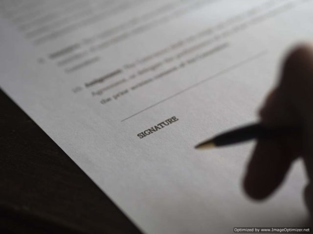 IMAGE: Picture of person signing a document