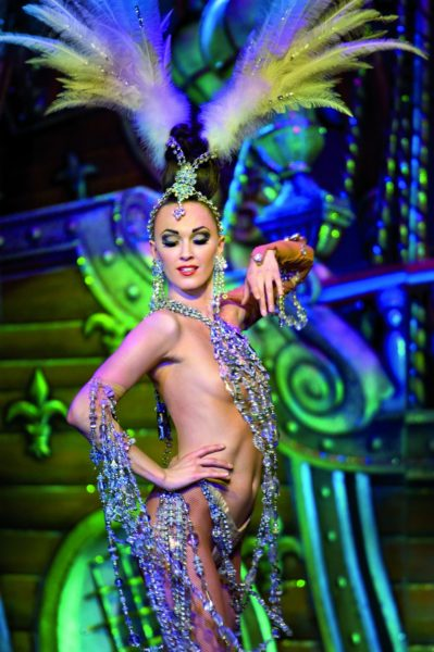 IMAGE: Dancer at the Moulin Rouge wearing spectacular costume with green and purple feathers