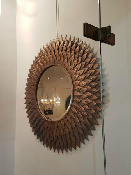 IMAGE: View through a window of a sunburst mirror at le Marché Aux Puces