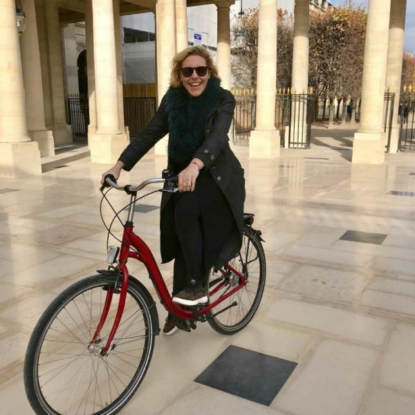 IMAGE: Founder and CEO of VINGT Paris, Susie Hollands, on her bicycle in Paris